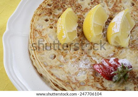 Shrove Pancake Tuesday pancakes with lemons and strawberries with yellow and blue napkins on white vintage shabby chic table, closeup. - stock photo