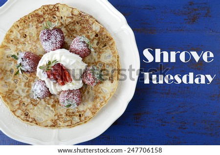 Shrove Pancake Tuesday pancakes with strawberries and cream on dark blue vintage shabby chic table, and text. - stock photo