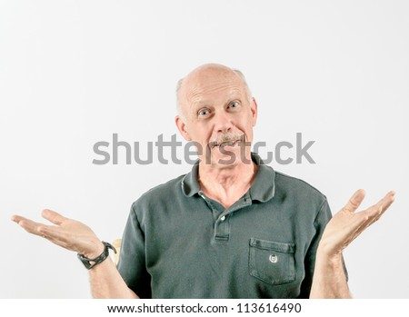shrugging bald smiling middle-aged man with a white mustache in dark golf shirt against a light plain background - stock photo