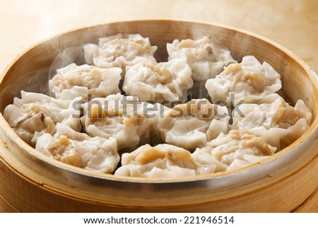 Shumai dumplings in a bamboo steamer - stock photo