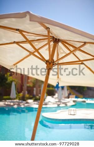 Shunhade umbrella near pool - stock photo