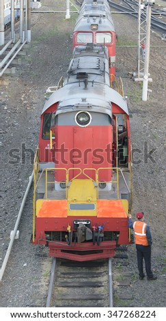 Shunting locomotive standing on rails at the train station. Nearby stands a railway worker in overalls. Front view from the top. - stock photo