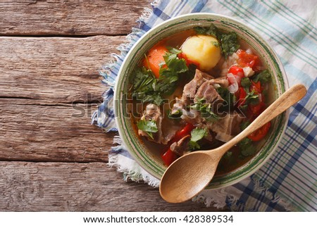 Shurpa lamb soup with vegetables closeup at the plate on the table. Horizontal view from above