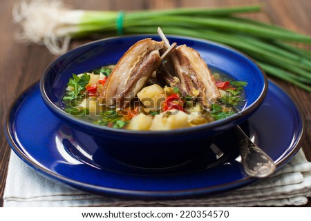shurpa - mutton soup in blue plate on a wooden table