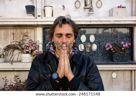 shut eyes man praying at the cemetery - stock photo