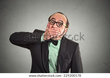 Shut up mouth, keep corporate deals secret. Portrait man worker employee covering his mouth. Speak no evil concept isolated grey background. Human emotion face expression feeling sign body language - stock photo