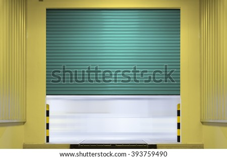 Shutter door or roller door outside factory building use for industrial background. Shutter door use for industrial building such as factory garage and warehouse.  - stock photo