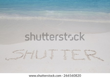 SHUTTER  letters writing on the sand beach and crystal clear water - stock photo