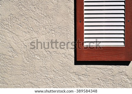 Shutter on stucco exterior wall - stock photo