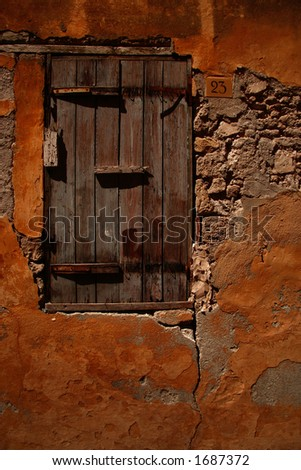 shutter window down warm and old cobbled backstreet in the old town of rhodes, could be and mediterranean street, greece, Italy etc... - stock photo