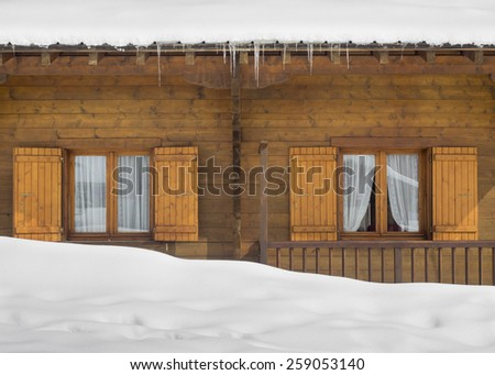Shuttered Cabin Windows Behind A Snow Drift Below Covered Roof With Icicles