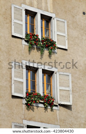 Shuttered windows bedecked with flowers in a small European village. - stock photo