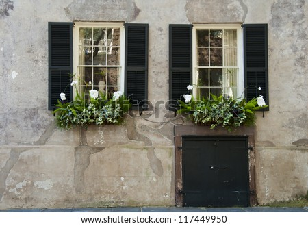 Shuttered windows in the stucco wall of an eighteenth century house. - stock photo