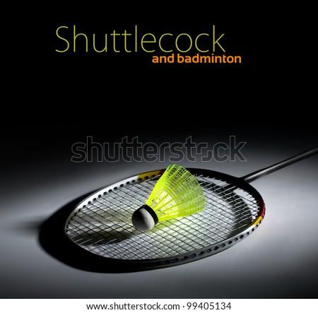 Shuttlecock and badminton on dark background - stock photo