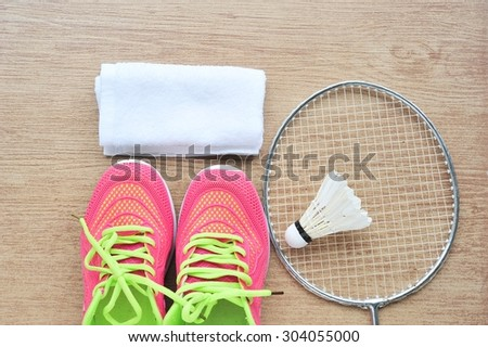 Shuttlecock and badminton racket  with shoe and towel on tile floor.