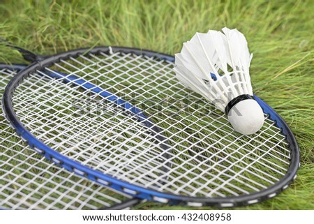 Shuttlecock and rackets on the green grass. Equipment for the game in badminton. - stock photo