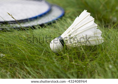 Shuttlecock with two rackets for badminton on the grass. Active summer holiday outdoors. - stock photo