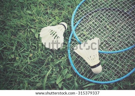 Shuttlecocks with badminton racket on green grass