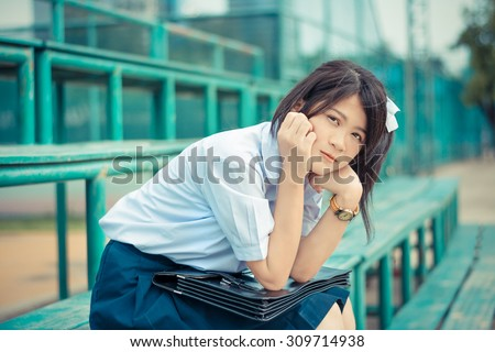 Shy Asian Thai schoolgirl student in high school uniform education fashion is sitting on a metal stand and showing facial bashful expression in vintage color style - stock photo