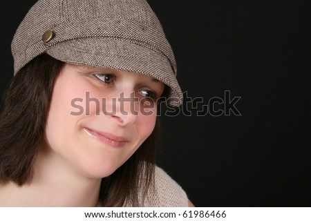Shy brunette female wearing a hat against black background