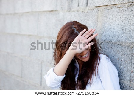 Shy brunette girl covering her face with a grey wall of background - stock photo