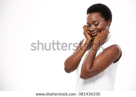 Shy cute african american young woman standing and touching her cheeks over white background - stock photo