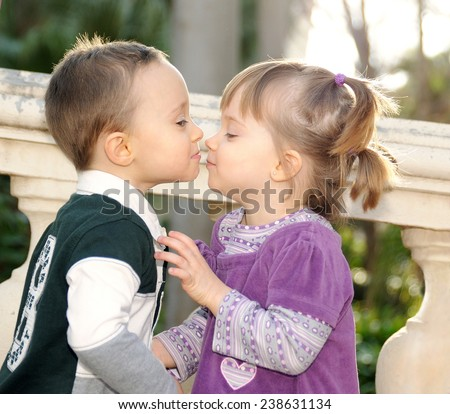 shy girl and boy kissing tenderly in the park - stock photo