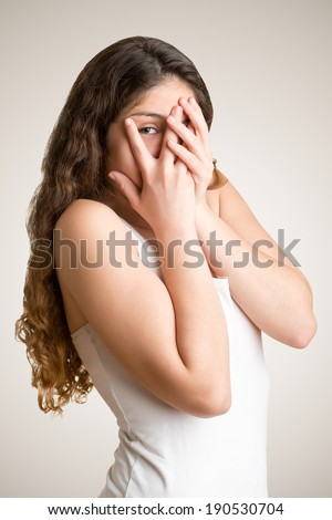 Shy girl covering up her face with her hands, isolated