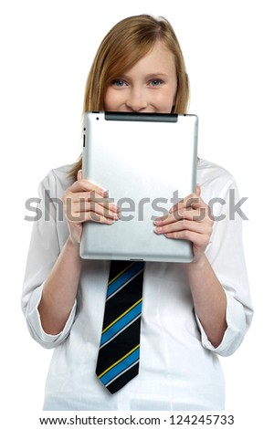 Shy girl hiding her face with a tablet device. Wearing school uniform.