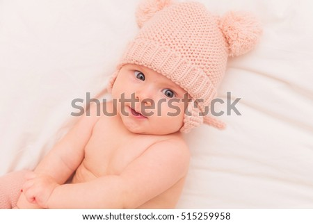shy litthe baby girl wearing knitted bear hat looking at the camera