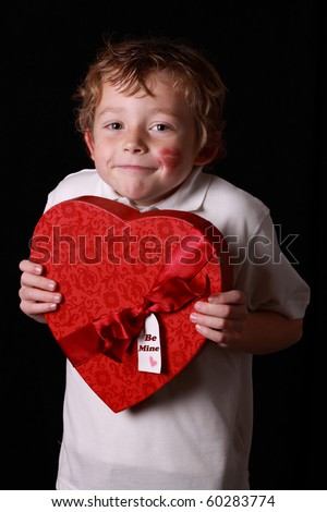shy little boy holding a Valentine box of chocolates
