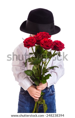 Shy little boy in black hat with bouquet of red roses, isolated on white