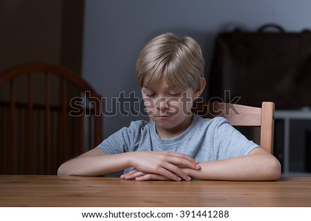 Shy little boy sitting at the table - stock photo