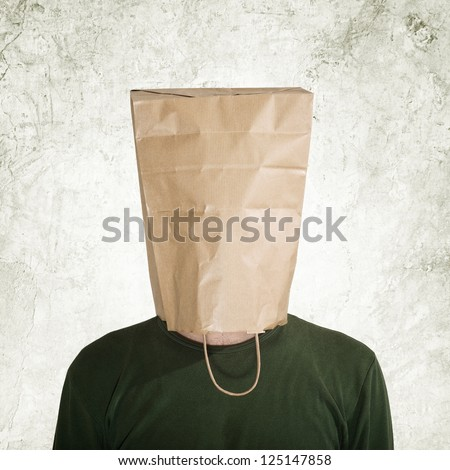 Shy man. Head in the paper bag. Man hidden behind the shopping bag. - stock photo