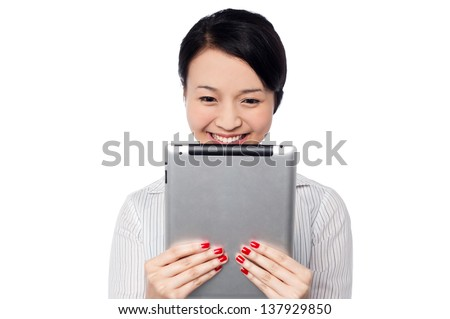 Shy smiling asian businesswoman holding tablet pc. Isolated on white.