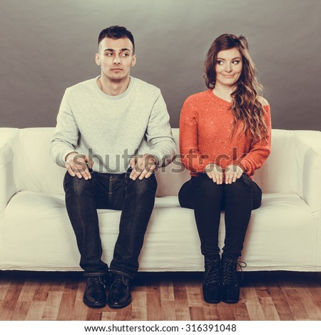 Shy woman and man sitting on sofa couch. First date. Attractive girl and handsome guy meeting dating and trying to talk. Instagram filtered. - stock photo
