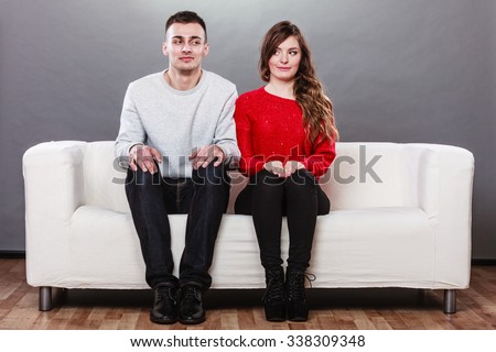 Shy woman and man sitting on sofa couch next each other. First date. Attractive girl and handsome guy meeting dating and trying to talk. - stock photo