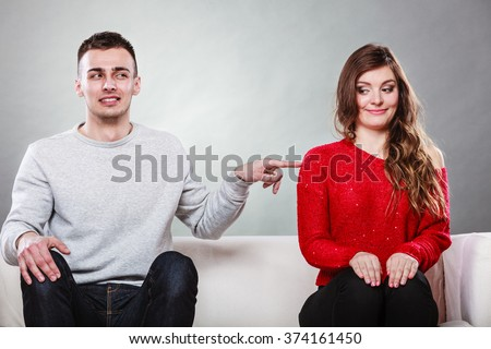Shy woman and man sitting on sofa couch next each other. First date. Attractive girl and handsome guy meeting dating and trying to talk. Male touching picking up female. - stock photo