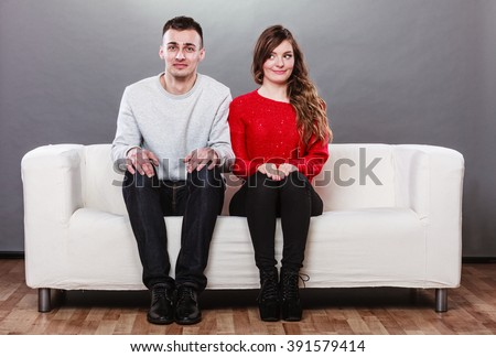 Shy woman and man sitting on sofa couch next to each other. First date. Attractive girl and handsome guy meeting dating and trying to talk. - stock photo
