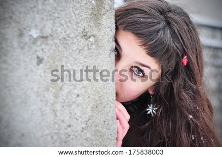 Shy woman hiding behind wall, face laughing timid