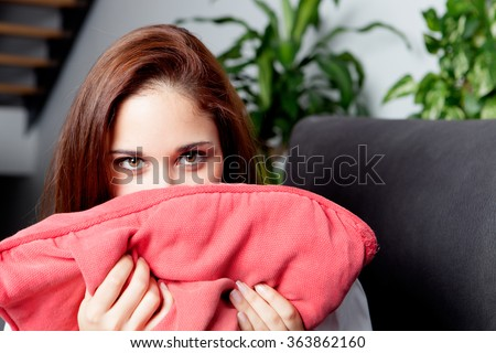Shy woman hiding her face cushion on the couch at home - stock photo