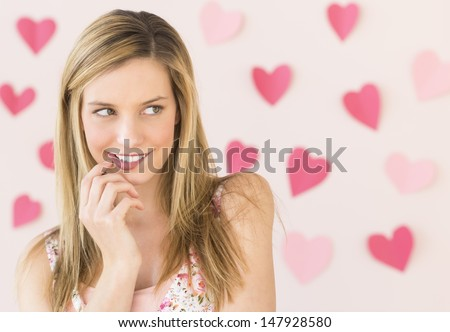 Shy young woman biting lip while looking away with heart shaped papers stuck against colored background - stock photo