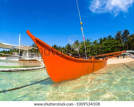 Siargao, Mindanao -  Philippines - March 1, 2016: A bright red fishing boat and net is docked on the scenic beach village of Daku Island, Siargao - Mindanao.