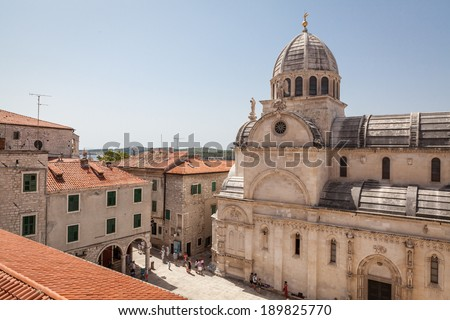 SIBENIK, CROATIA - AUGUST 6, 2012: View at the 15th century Cathedral of St. James in historic center of Sibenik, with nearby buildings and tourists strolling around. - stock photo