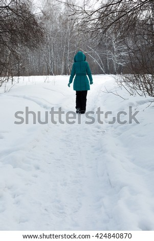 Siberia. A woman walks along the path in a birch forest on a Sunny day. - stock photo