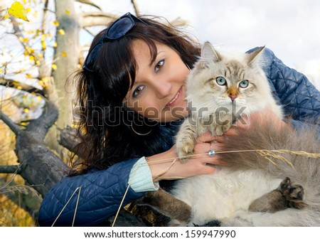 Siberian cat and young woman in a autumn forest - stock photo