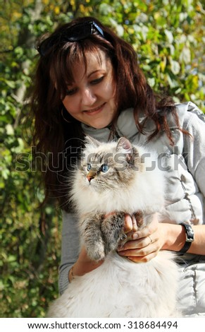 Siberian nevsky masqarade cat and young woman in a  autumn nature - stock photo