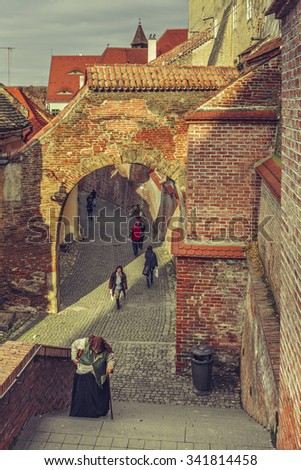 SIBIU, ROMANIA - 12 NOVEMBER, 2015: People wander along the backstreets with old fortified brick arcades and walls in the historic Lower Town of Sibiu city, European Capital of Culture in 2007. - stock photo