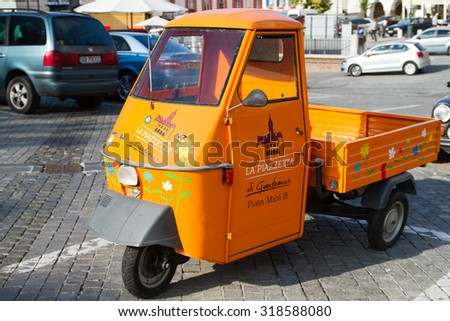 SIBIU - SEPTEMBER 09: Funny, colored food delivery car in the center of Sibiu, city designated the European Capital of Culture for the year 2007. Sibiu, Romania on 09 September 2015 - stock photo