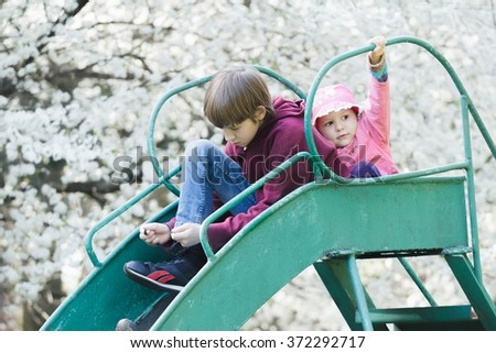 Sibling brother and sister sitting on old metal playground slide at blossoming spring fruit tree background